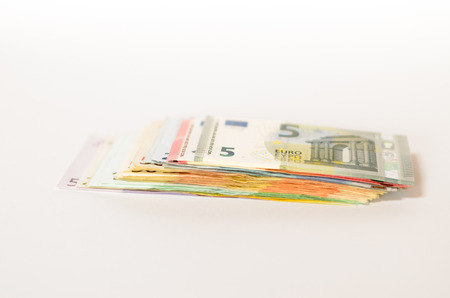 denominations: Pile of used Euro notes of assorted denominations stacked on top of one another on a white background with copyspace in a conceptual financial image