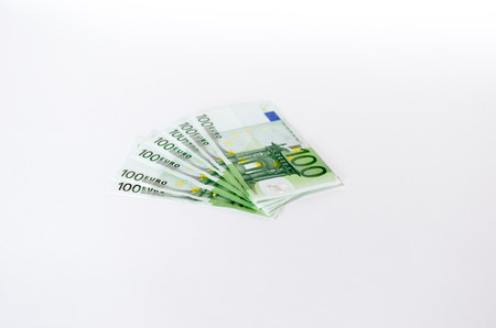 fanned: Wad of used 100 Euro notes fanned out on an off-white studio background with copyspcae in a conceptual economic and financial image