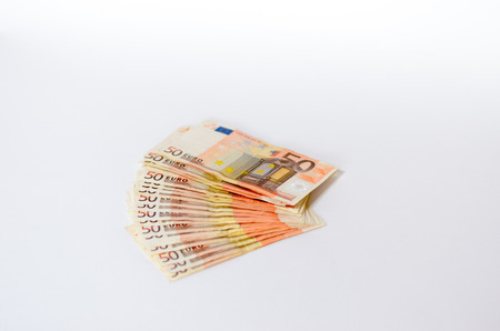 fanned: Wad of used 50 Euro notes fanned out on an off-white studio background with copyspcae in a conceptual economic and financial image Stock Photo