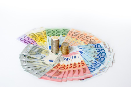 fanned: Artistic arrangement of Euro notes and coins with Euro banknotes of different denominations arranged in a fanned circle around the stacked coins on a white background in a conceptual financial image