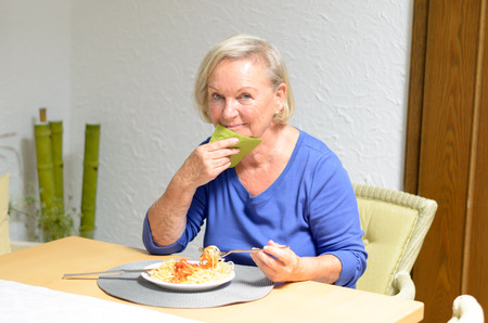 oldage: Senior woman sitting at a table eating a meal with a happy smile of appreciation