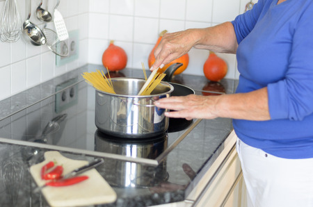 Lady cooking spaghetti pasta on her stove adding the noodles to the boiling water as she prepares tasty Italian cuisine Stock Photo