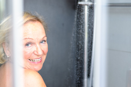 attractive charismatic: Smiling attractive senior woman taking a shower looking through the open door of the shower cubicle and smiling at the camera