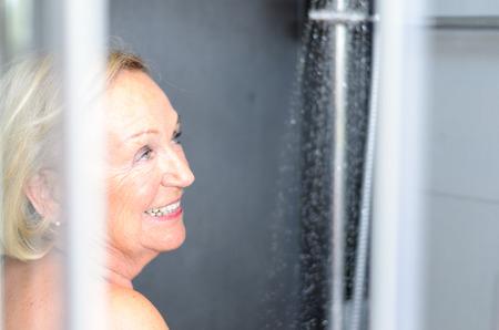 mujer bañandose: Sonriente atractiva mujer mayor que toma una ducha mirando a través de la puerta abierta de la cabina de ducha y sonriendo a la cámara Foto de archivo