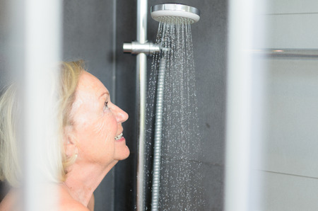 shower cubicle: Smiling attractive senior woman taking a shower looking through the open door of the shower cubicle and smiling at the camera