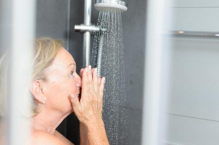 샤워 칸막이의 문을 열고 샤워를하고 카메라로 웃는 샤워를 복용 매력적인 수석 여자를 웃고