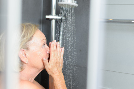 Smiling attractive senior woman taking a shower looking through the open door of the shower cubicle and smiling at the camera