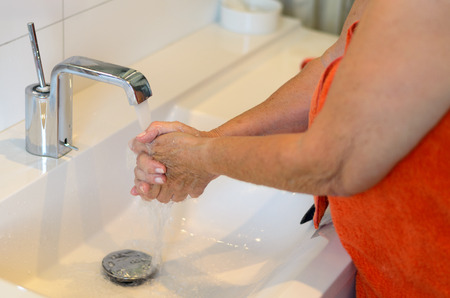 rinsing: Woman washing her hands at the sink rinsing off the soap under the running water from the faucet Stock Photo
