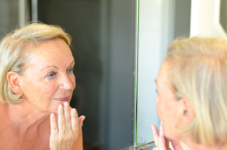 Senior lady checking her skin in the mirror leaning forwards for a closer look as she hold a finger to her forehead