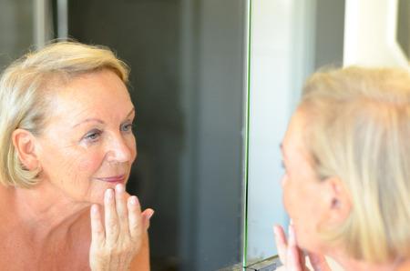 mirror?: Señora mayor control de su piel en el espejo se inclina hacia delante para ver mejor como ella mantenga un dedo en la frente