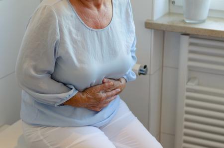 inodoro: Mediados de secci�n de la mujer mayor que llevaba pantalones blancos y una blusa de color azul claro que se sientan en el inodoro que sostiene el est�mago