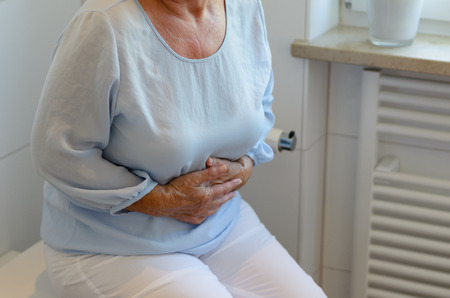 senior pain: Mid section of senior woman wearing white trousers and light blue blouse sitting on toilet holding stomach