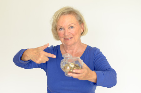 oldage: Smiling senior woman holding a glass piggy bank filled with loose coins in her hands extended her nestegg for a dream purchase