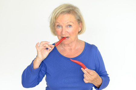 Senior woman biting a fresh red hot chili pepper while looking at the camera with a smile upper body over a gray background