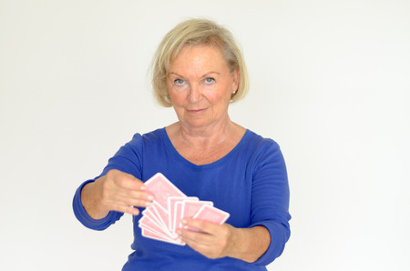 oldage: Smiling woman holding a fanned hand of playing cards Selecting one from the pack with a smile upper body over gray