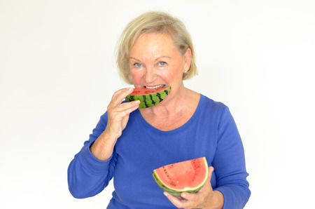 oldage: Elderly lady enjoying a slice of fresh watermelon biting into the sweet juicy pulp as she smiles at the camera upper body over gray