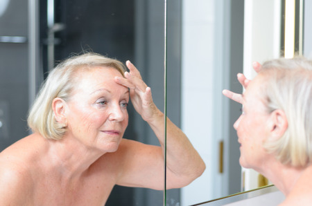 oldage: Senior lady checking her skin in the mirror leaning forwards for a closer look as she hold a finger to her forehead