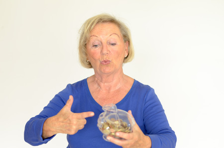 nestegg: Smiling senior woman holding a glass piggy bank filled with loose coins in her hands extended her nestegg for a dream purchase
