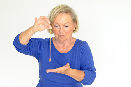 Attractive blond elderly woman holding a pendulum over her hand in a fortune telling divination or hypnosis concept Stock Photo