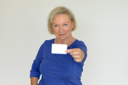 oldage: Elderly attractive lady holding out a blank business card towards the camera with copy space for your details and text over a gray background