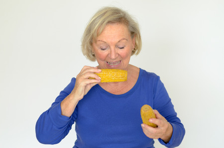oldage: Elderly lady enjoying fresh corn on the cob biting into the kernel with a happy smile in a healthy diet concept over gray Stock Photo