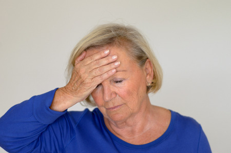 throbbing: Senior lady suffering with a headache or fever holding her hand to her forehead with her eyes closed in pain head and shoulders over gray Stock Photo