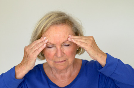 Senior lady suffering with a headache or fever holding her hand to her forehead with her eyes closed in pain head and shoulders over gray Foto de archivo