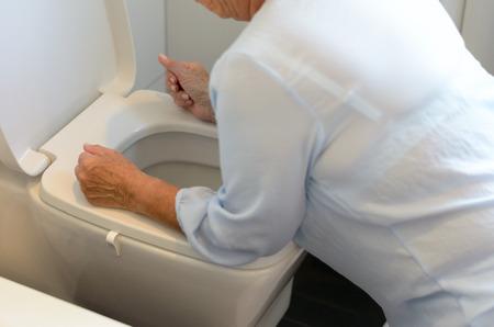 vomito: Mujer que consigue enfermo y vómitos en un inodoro de rodillas con los brazos apoyados en el asiento de vista de cerca de su cuerpo