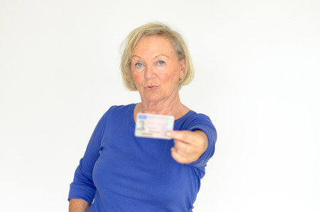Senior lady holding out her drivers license at arm39s length towards the camera with a serious expression focus to her face over gray Foto de archivo