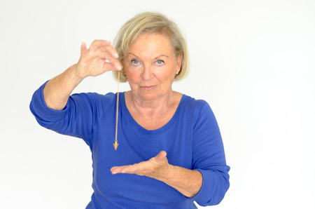 hypnotise: Attractive blond elderly woman holding a pendulum over her hand in a fortune telling divination or hypnosis concept Stock Photo