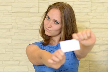 qualifications: Young woman holding out a blank white business card in her extended hands with copy space for your contact details and qualifications branding with focus to the eyes