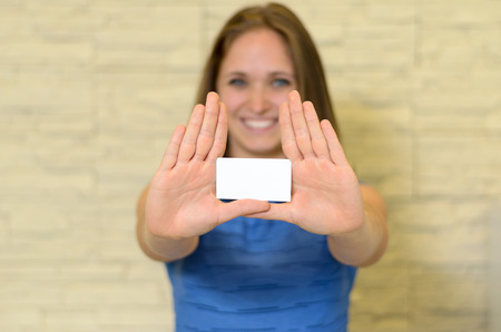 qualifications: Young woman holding out a blank white business card in her extended hands with copy space for your contact details and qualifications branding with focus to the card Stock Photo