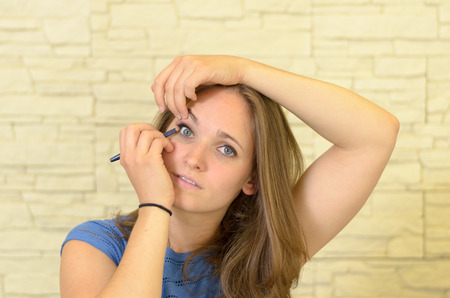 enhance: Pretty young woman applying eyeliner to her eye to enhance and outline the eye in a fashion and beauty concept Stock Photo