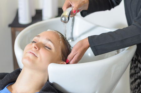 shampooing: Young woman at the hairdressing salon having her hair washed and shampooed at a basin by the stylist prior to cutting smiling at the camera