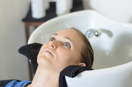 lying on back: Young woman in a hairdressing salon lying back with her head in the basin waiting for her hair to be shampooed before cutting it