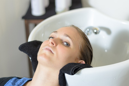 pampered: Young woman in a hairdressing salon lying back with her head in the basin waiting for her hair to be shampooed before cutting it