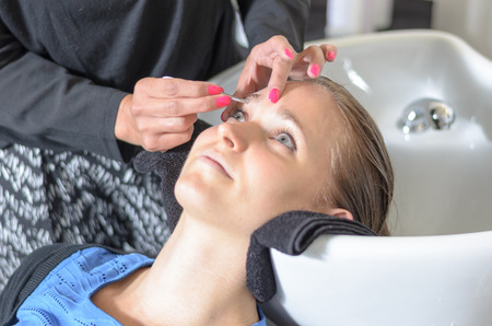 eyebrow trimming: Beautician trimming a young girls eyebrows with a pair of tweezers as she relaxes with her head in the basin closeup of her face