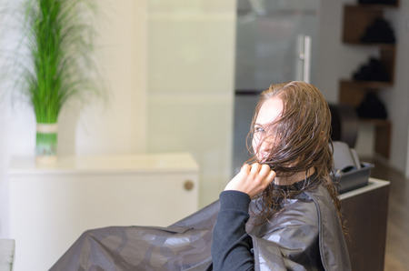 haircutting: Serious Young Woman Wearing Salon Haircutting Cape Sitting Inside the Parlor Looking at the Camera. Stock Photo