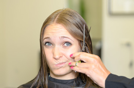 dubious: Young woman giving the hairdresser a dubious look as she prepares to cut short her long brown hair with a pair of scissors humorous expression Stock Photo