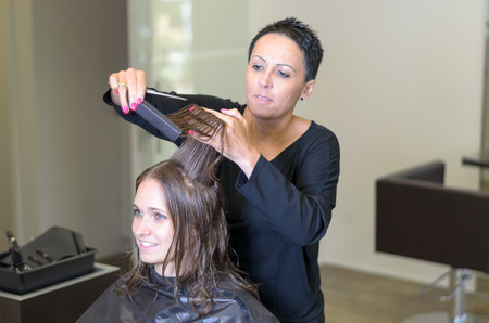 snipping: Professional hairdresser trimming the long brown hair of a young woman in her hairdressing salon snipping the ends with a pair of scissors in a hair care and beauty concept Stock Photo