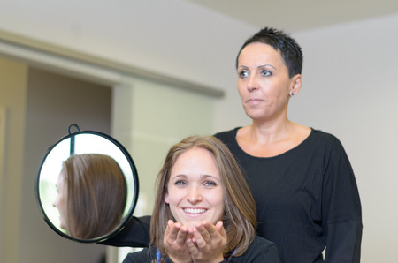 elated: Happy Female Customer In a Salon Sitting In Front A Hairdresser Woman Holding A Round Mirror Smiling at the Camera After styling her hair.