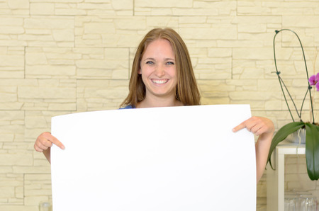 saleslady: Pretty woman holding up a blank white sign in front of her chest as she gives the camera a lovely smile copyspace for your text or advertising