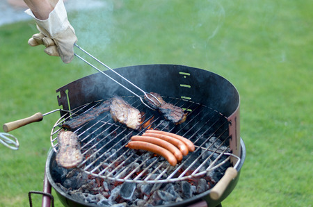 long handled: Person wearing a glove using long handled tongs to grill spicy sausages over a portable barbecue outdoors on green grass at a summer picnic or campsite