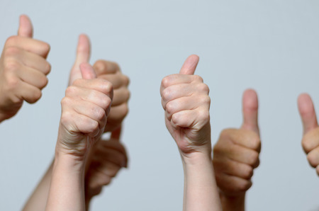 Group of enthusiastic men giving thumbs up gestures of approval, success and support, close up view of their hands against a grey background