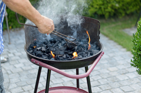 grill tongs sausage: Man standing outdoors on a green lawn cooking meat on a portable barbecue with a pair of tongs, close up view of the grill and his center body Stock Photo