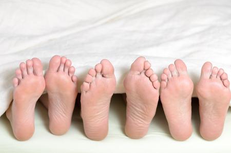 Drei Paare Füße im Bett, alle auf der Suche nach oben