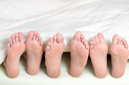 Three pairs of feet in bed, all looking upwards Stock Photo