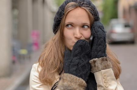かなりブロンド若い女性を着て冬ファッションを彼女の口との距離を見て、通りながらカバーで携帯電話で誰かと話を閉じます。