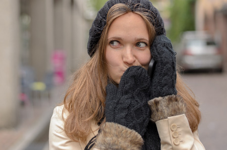 Close up Pretty Blond Young Woman Wearing Winter Fashion, Talking to Someone on Mobile Phone at the Street While Covering her Mouth and Looking Into Distance. Banco de Imagens - 42431452