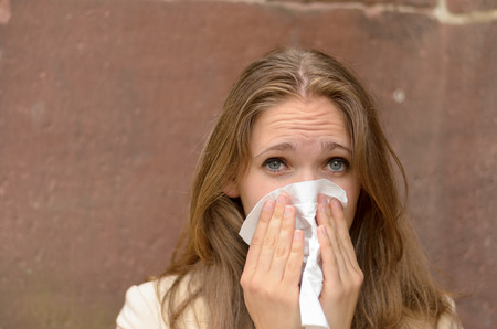 sniffles: Young woman blowing her nose on a handkerchief conceptual of an illness, flu, cold, allergic rhinitis or hay fever